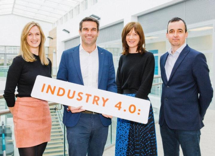 Two women and two men holding a sign saying Industry 4.0 in a brightly lit room.