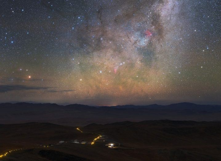 A stunning night sky shot filled with stars, with a lit-up road on Earth leading towards the horizon.