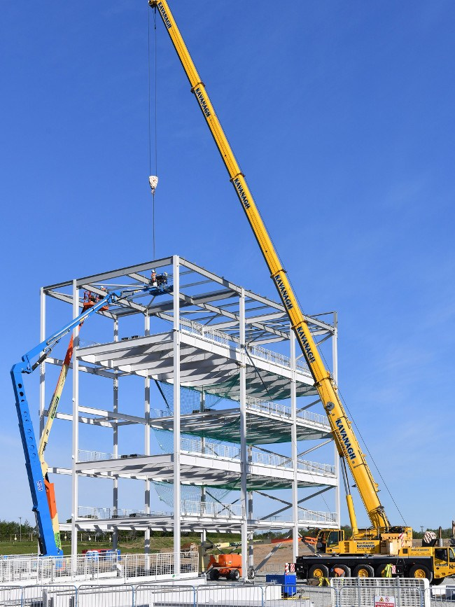Construction of a new pharmaceutical factory using a yellow crane, steel structure under a blue sky.