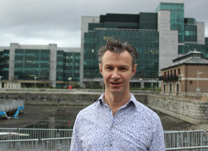 Man in patterned shirt standing in front of buildings in Dublin.