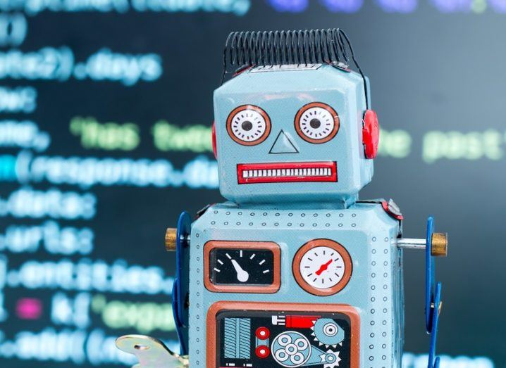 Blue, retro toy robot against a background of code on a computer screen.