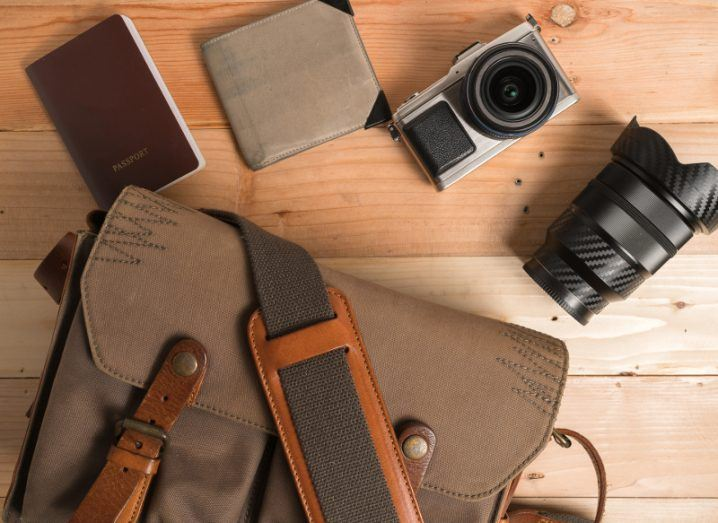 Overhead view of a camera, wallet, duffel bad and other travel paraphernalia on a wooden table.