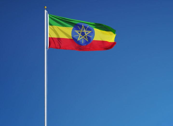 View of flag of Ethiopia billowing gently in the breeze against the backdrop of a cloudless sky on a sunny day.