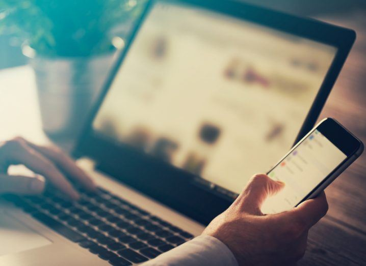 View of man's hands with smartphone in one hand and other hand floating over keyboard of laptop with social media on screen.