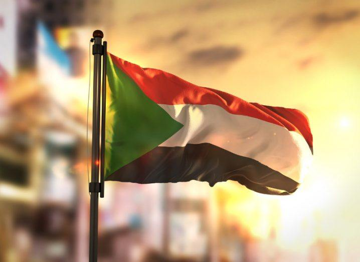 View of the flag of Sudan billowing in the breeze amid a sunset-drenched blurred backdrop possibly of a city.