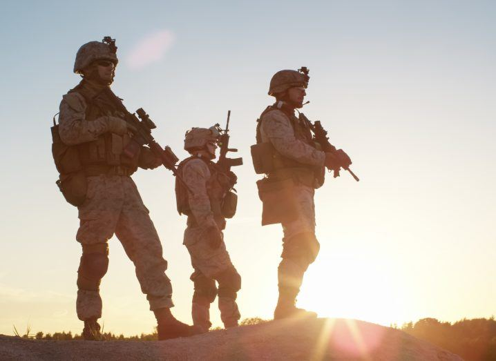View of armed soldiers standing on an arid desert peak looking ahead of them against the backdrop of sunrise.