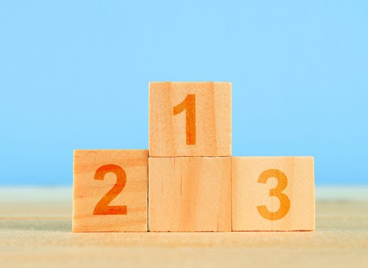 Wooden blocks fit together to form a winner's podium against a blue background.
