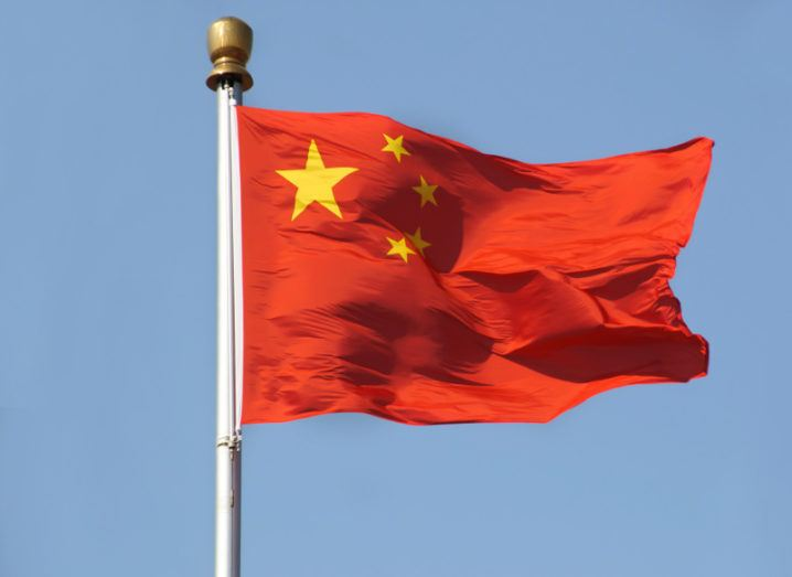 View of Chinese flag against cloudless sky billowing in the breeze.