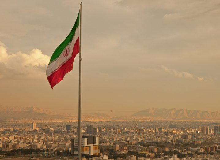 View of Iran flag billowing against Tehran skyline with arid desert hills in the distance.