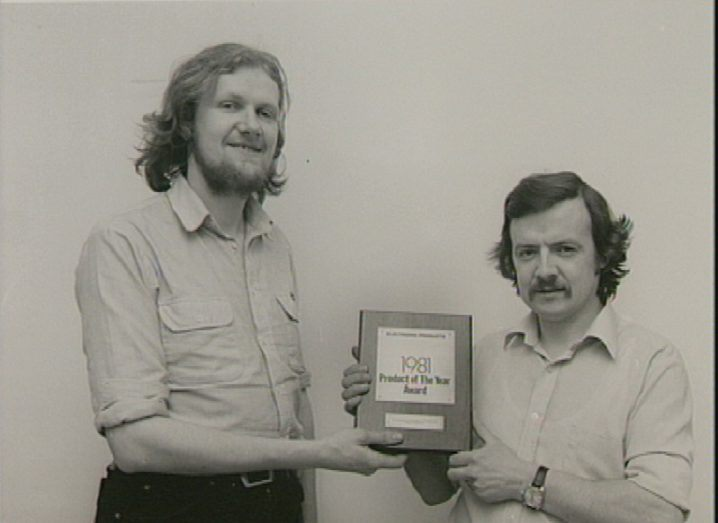 Black and white image of Mike Tuthill receiving an award for a product of the year in 1981.