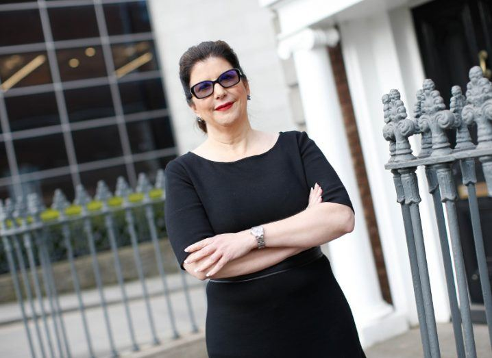 Woman in black dress wearing sunglasses standing with arms folded outside a building.
