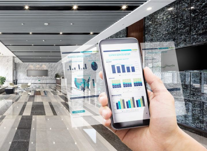 Smartphone holding key business data in a hall of a building.