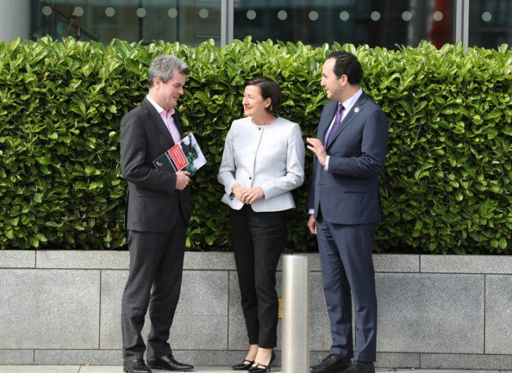 Two men and a woman stand in front of a neatly trimmed hedge outside a building, discussing a report that one of them is holding.