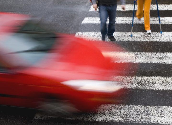 Blurred image of a red car driving through a pedestrian crossing with two people already crossing.