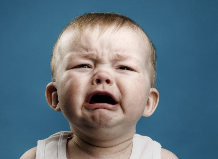 Close-up of a baby crying profusely in a white vest against a blue background.