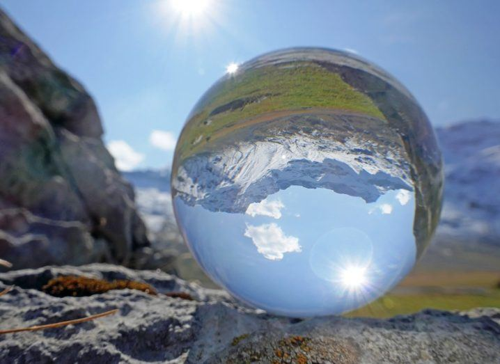 A crystal ball placed on a rock reflecting a mountain range and sunny sky.