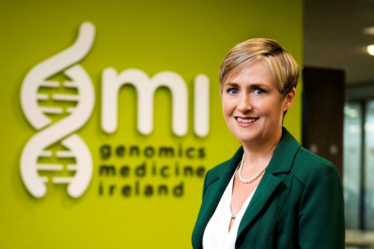 Woman with blonde short hair wearing a green suit and white blouse in front of lime green wall with GMI logo in white.
