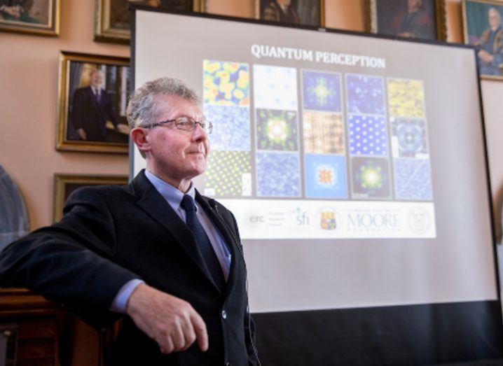 Prof Séamus Davis stands resting an elbow on a lectern in front of a projection of a slide depicting 'quantum perception'.