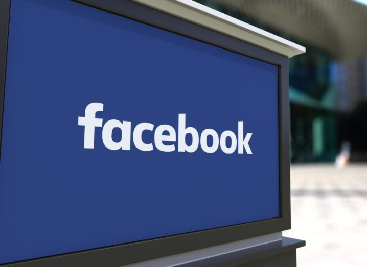 View of Facebook logo on street signage with blurred view of people walking in background.