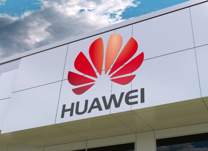 View of Huawei logo on a modern glass panel building facade with overcast and cloudy sky in background.