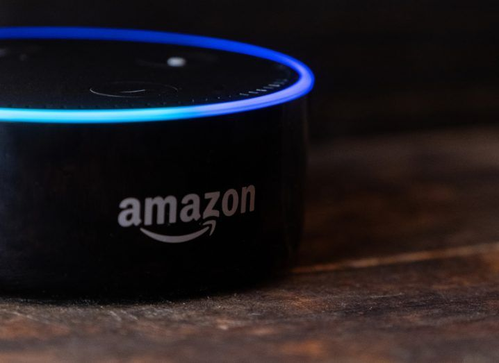 View of Alexa enabled Amazon echo dot, black small device with ring of neon blue light on table.