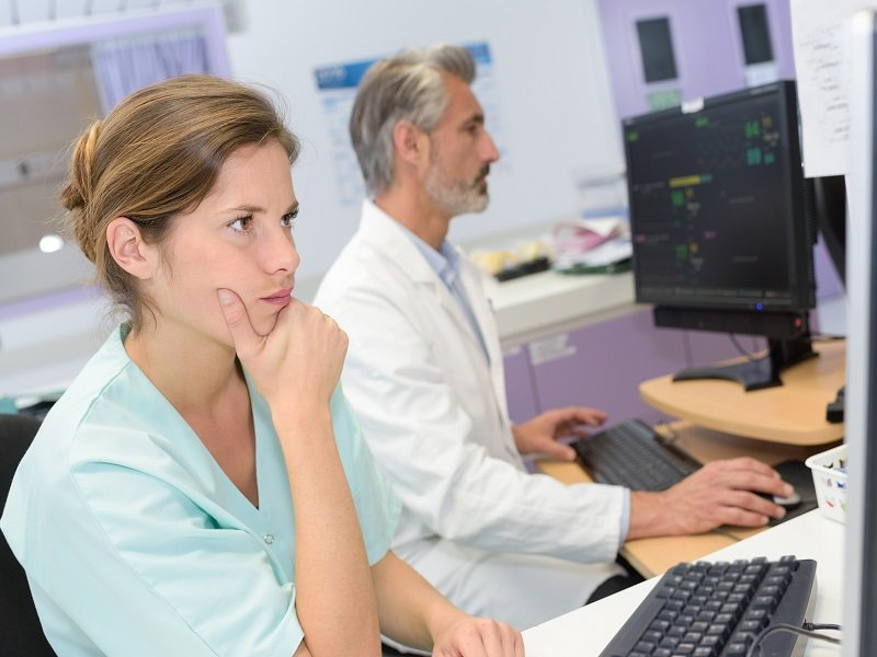 Two doctors analysing results on a computer screen.