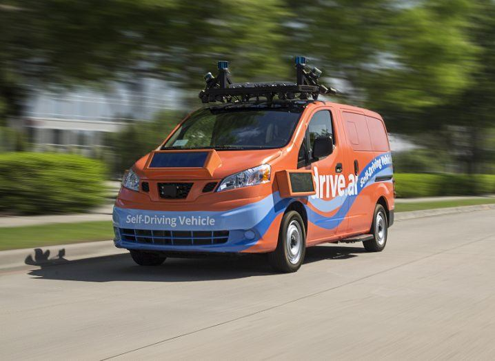 An orange and blue self-driving van with a roof-mounted vision system drives along a tree-lined road.