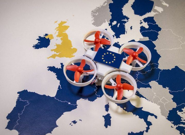 Small, white toy drone with red propellers on a map of Europe showing EU member states.