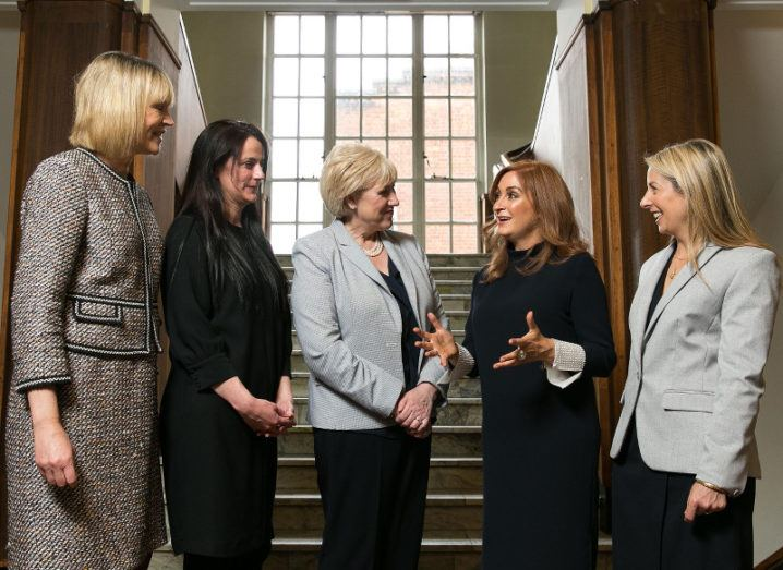 Five smartly dressed women stand in deep discussion at the bottom of a staircase.