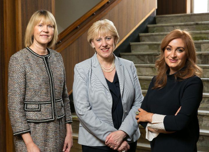 Three women in business attire pose for a photo at the bottom of a staircase.