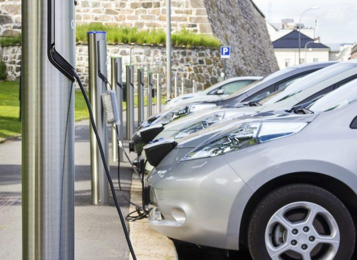A number of silver EVs in a row charging at public charging points with an old brick wall in the background.