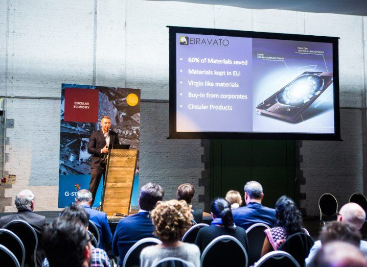 Marcin Kulik stands in front of an audience on a stage presenting his company, Eiravato.