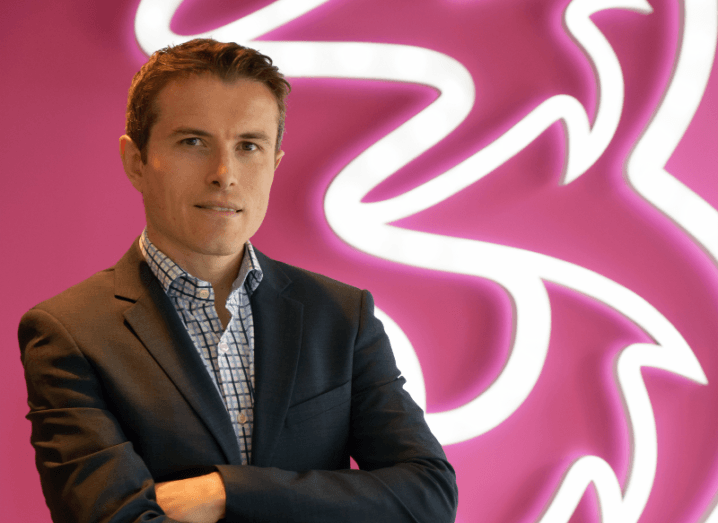 Eoin Kealy in a suit standing with his arms folded in a front of a neon pink wall lit up with a large LED Three logo.