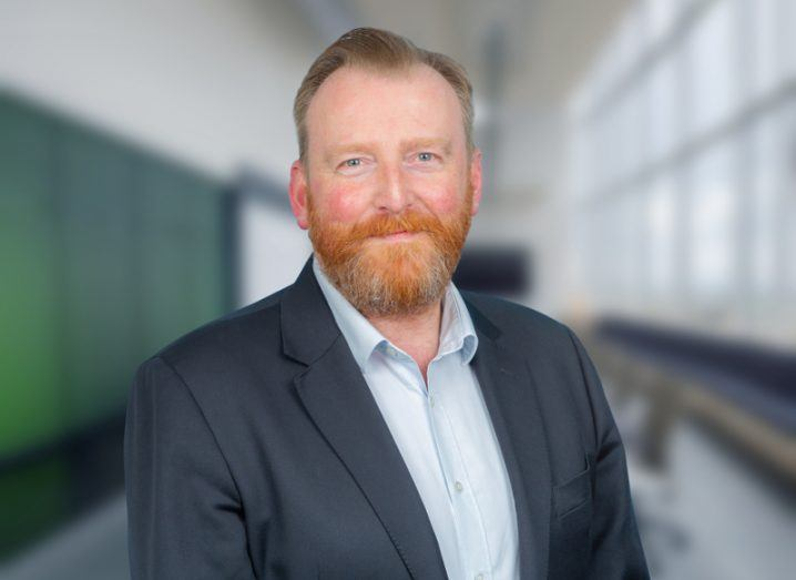 Man with red hair and red beard wearing a navy jacket and blue shirt.