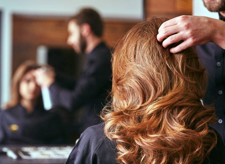 The back of a woman's head getting her hair done with a reflection of her face in a mirror in the background.