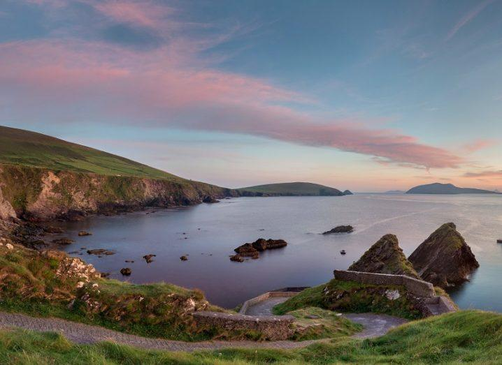 Scenic, panoramic shot of rocks and a steep road descending to a quay against a dusk sky.