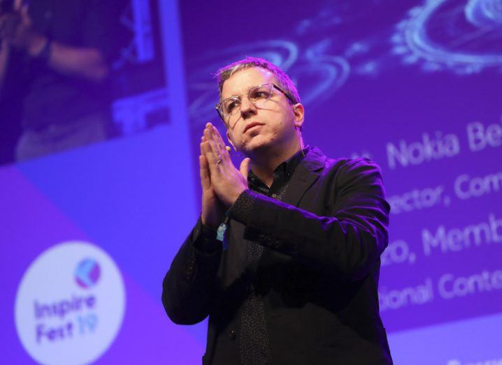 Man with glasses with hands clasped together thoughtfully against purple Inspirefest stage backdrop.
