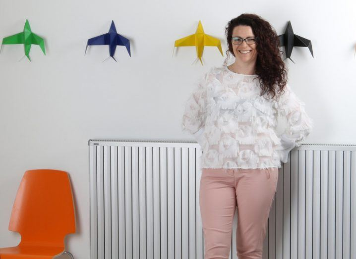 Karina Kelly, founder of Mypicdrop, stands against a white wall decorated with large, colourful origami birds.