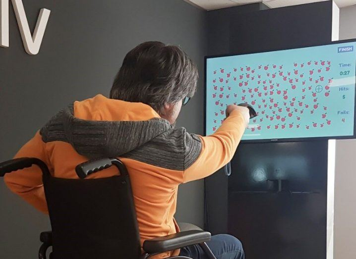 View of man in wheelchair with arm up holding remote using VR stroke rehabilitation game.