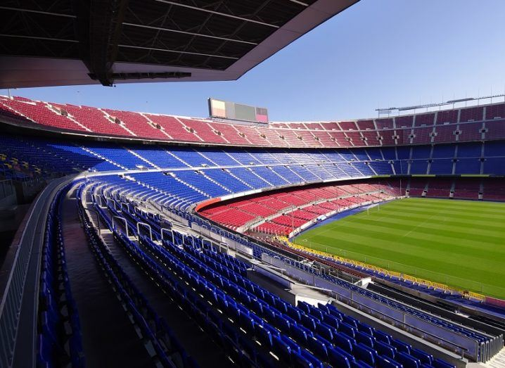 A wide view of an empty Camp Nou stadium, home of FC Barcelona, with red and blue seating against a sunny sky.