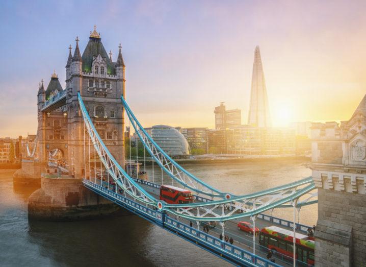 A red bus crosses London bridge as sun rises over the Shard building.