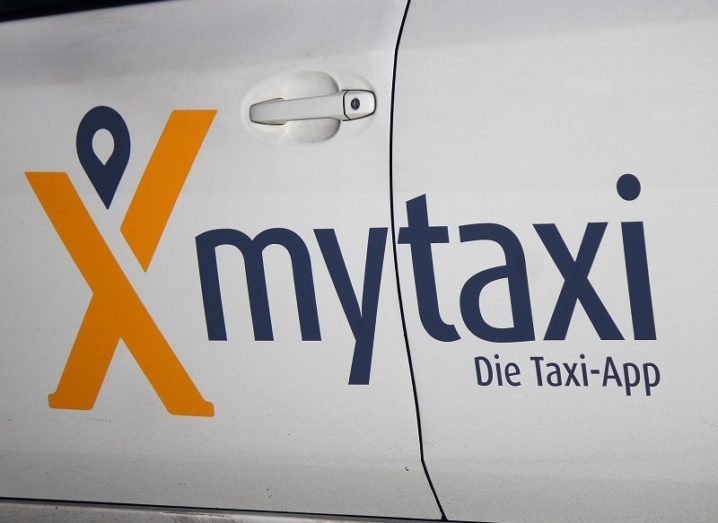 Close-up of the Mytaxi logo on the side of a white car door.