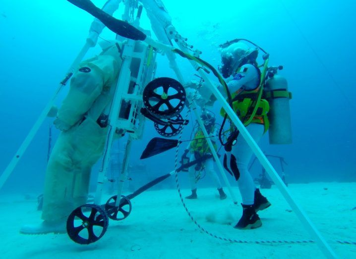 An astronaut in a spacesuit underwater attempting to carry a spacesuit on the LESA rescue device.