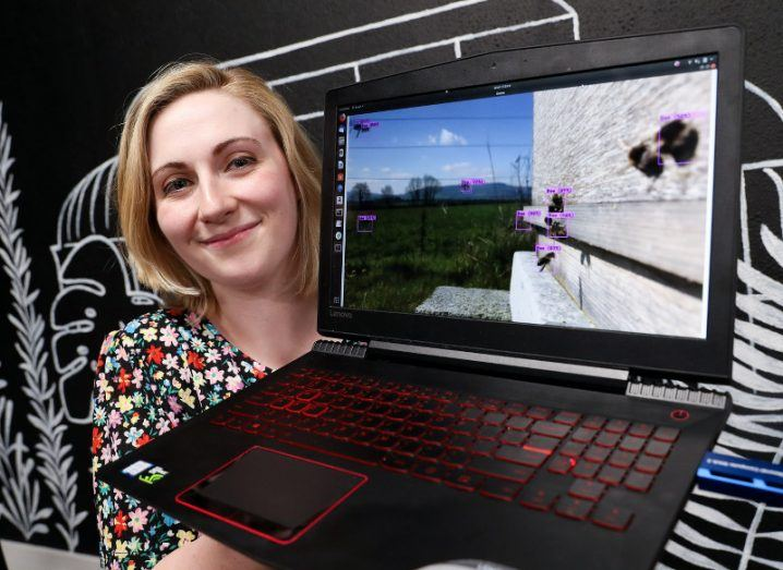 A blonde woman in a floral dress holds up a laptop displaying footage of bees being identified with markers via machine vision technology.