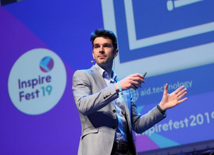 Niall Dennehy in a grey blazer and white shirt on stage against the purple branding of Inspirefest.