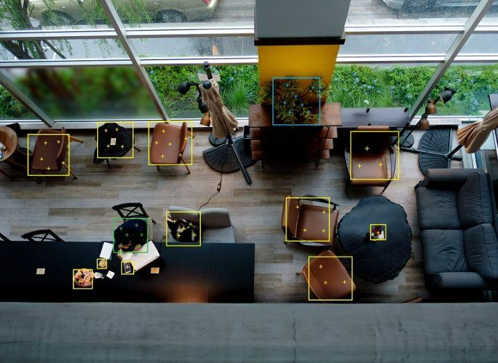 Digitally rendered object recognition boxes placed on an overhead view of an office with chairs, sofas and a person at a desk.