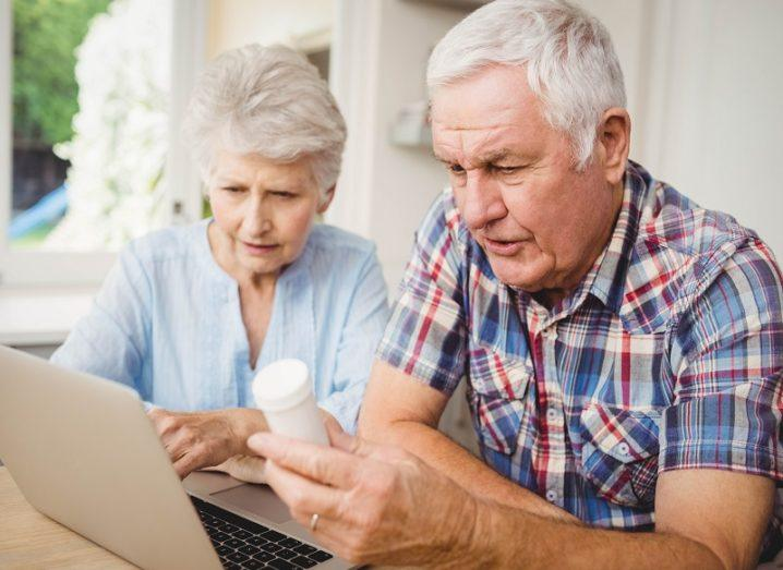 An elderly man holding a white pill bottle with an elderly woman looking at a laptop.