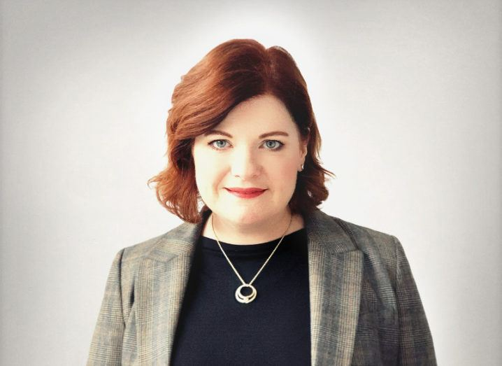 woman with short red hair and red lipstick, wearing black top, grey blazer and silver pendant, against light grey background.
