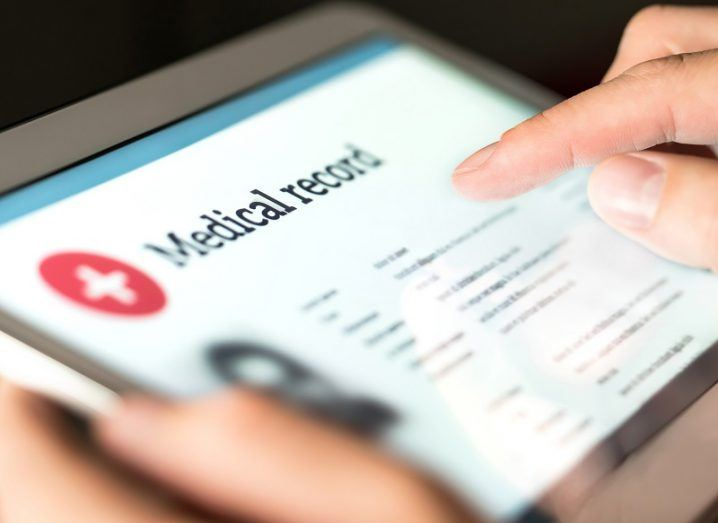 Person on a tablet with a patient's medical record on screen.