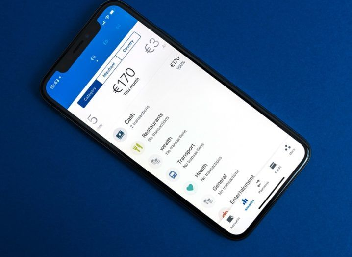 The Revolut app with bank balance open on an iPhone X against a navy blue background.